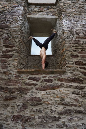 Young man exercising on stone wall