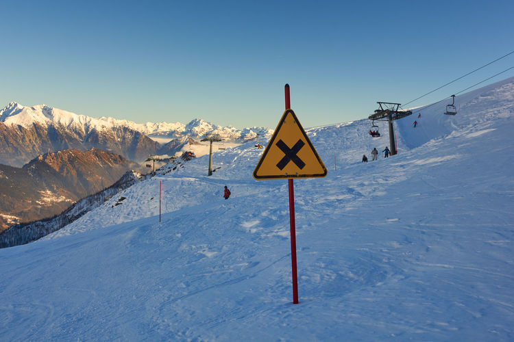 Alpine Holiday Sun North Europe Vacation Safety Landscape Top Seasonal Motivational RISK Italy Symbol Aspen Peak Metal Snow Winter Skier Motivation Nature Mountain Signboard Country Color Frost White Resort Sky Stay Fit Sign Blue Background Season  Information Outdoor Yellow Ice Warning Ski