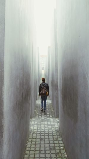 Into the light Perspective Light Walking Backpack Girl Memorial Berlin Art Installation Architecture One Person Rear View Built Structure Full Length Lifestyles The Mobile Photographer - 2019 EyeEm Awards Real People The Way Forward Building Exterior Footpath Wall - Building Feature City Life City Diminishing Perspective