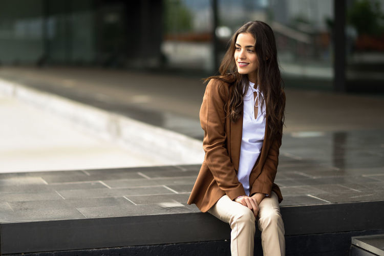 Smiling young businesswoman sitting on retaining wall