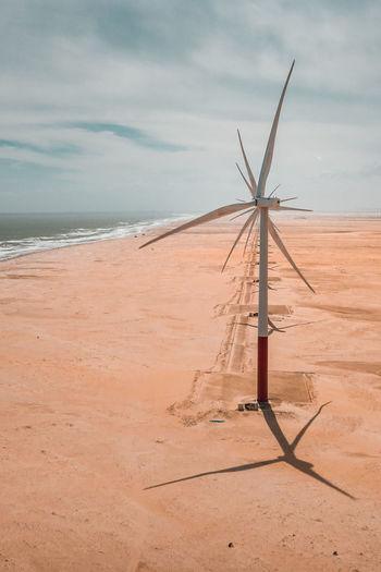 Windmills at beach against sky