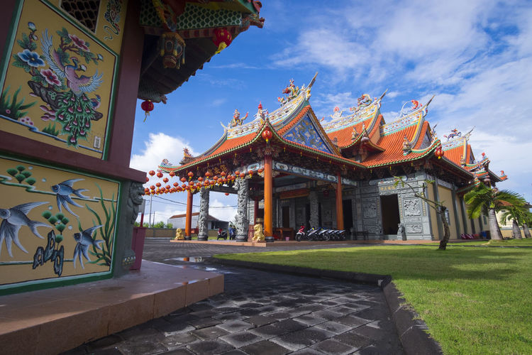 Benoa, Bali, Indonesia - January 28, 2017 : People praying and wishing a happy chinese new year on vihara satya dharma. Architectural Column Architecture Art And Craft Belief Building Building Exterior Built Structure Cloud - Sky Day Nature No People Ornate Outdoors Place Of Worship Plant Religion Sky Spirituality Sunlight Travel Destinations