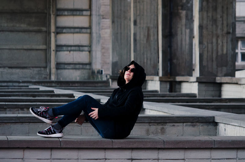 Side view of woman wearing sunglasses while sitting below bridge