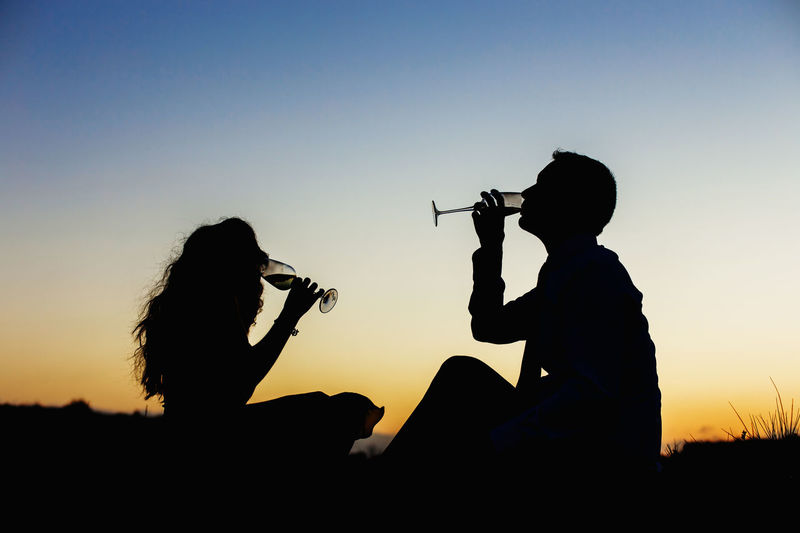 Silhouette couple having drinks against clear sky during sunset
