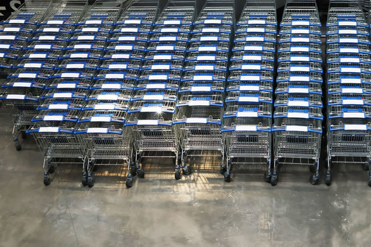 Many row of empty shopping carts waiting for customers. Absence Built Structure Chair Cold Temperature Consumerism Day Empty In A Row Large Group Of Objects Metal Nature No People Order Outdoors Repetition Seat Shopping Cart Side By Side Winter