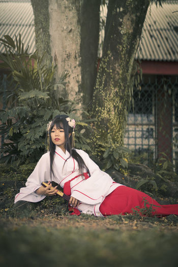 Young woman wearing traditional clothing while sitting on land