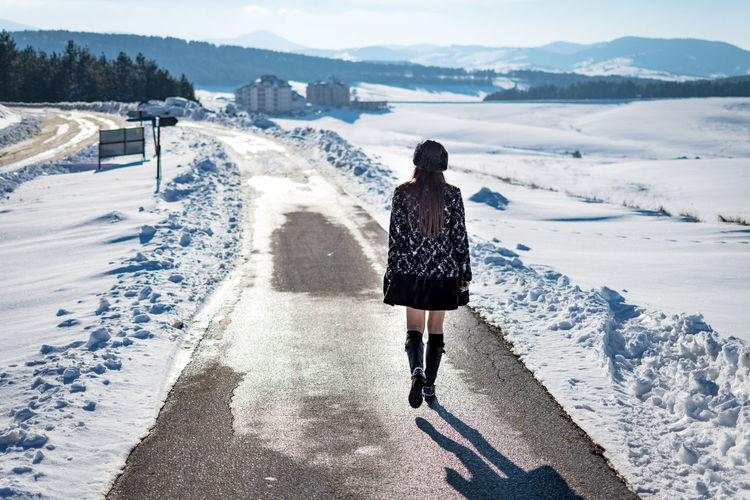 One Person Rear View Real People Winter Lifestyles Full Length Cold Temperature Leisure Activity Snow Nature Day Standing Water Clothing Warm Clothing Mountain Women Architecture Outdoors