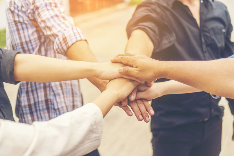 Close-up of friends stacking hands while huddling outdoors