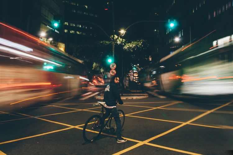 Blurred motion of man riding bicycle on road in city