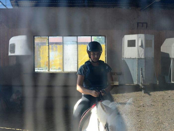 Woman Sitting On Horse In Stable