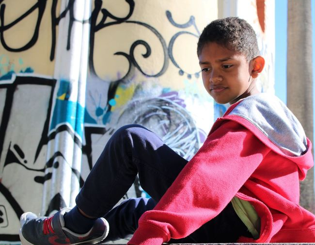 Boy sitting against graffiti wall