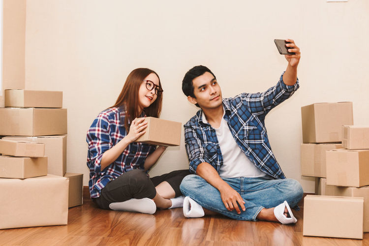 Happy couple with cardboard box at new home Adult Apartment Beginnings Box Boyfriend Cardboard Cardboard Box Casual Clothing Change Couple - Relationship Flooring Heterosexual Couple Indoors  Moving House Packing Relocation Sitting Technology Togetherness Two People Wireless Technology Young Adult Young Couple Young Men Young Women