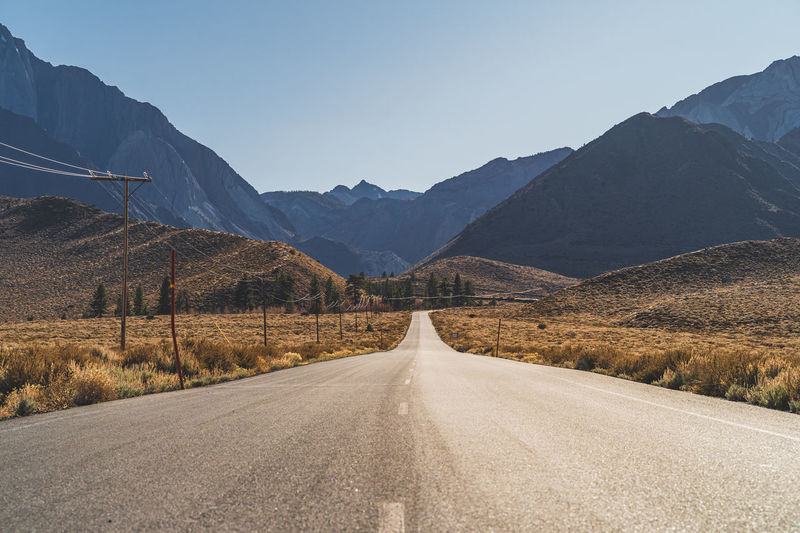 Two lane road in the arid sierra nevada's california leading to mountains against clear blue sky.