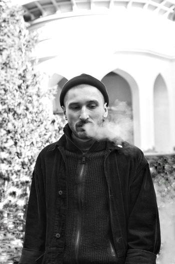 Man exhaling smoke in city