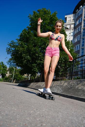 Full length of smiling woman standing on skateboard against building