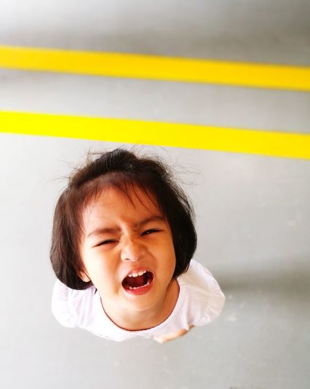 High angle portrait of girl making face indoors
