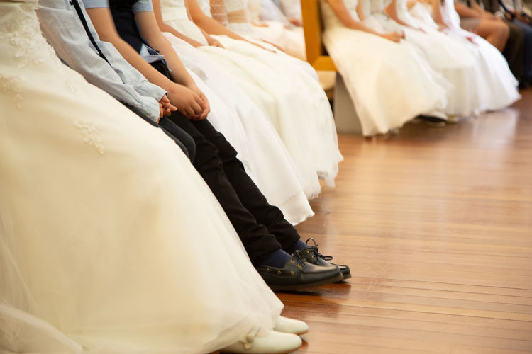 Low section of bridesmaids sitting at hardwood floor