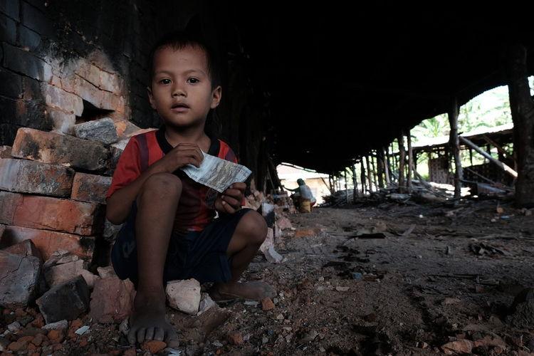 Portrait Of Boy Against Brick Wall