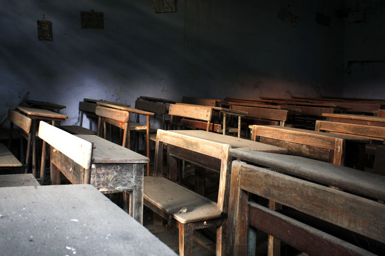 Empty wooden benches and table in classroom