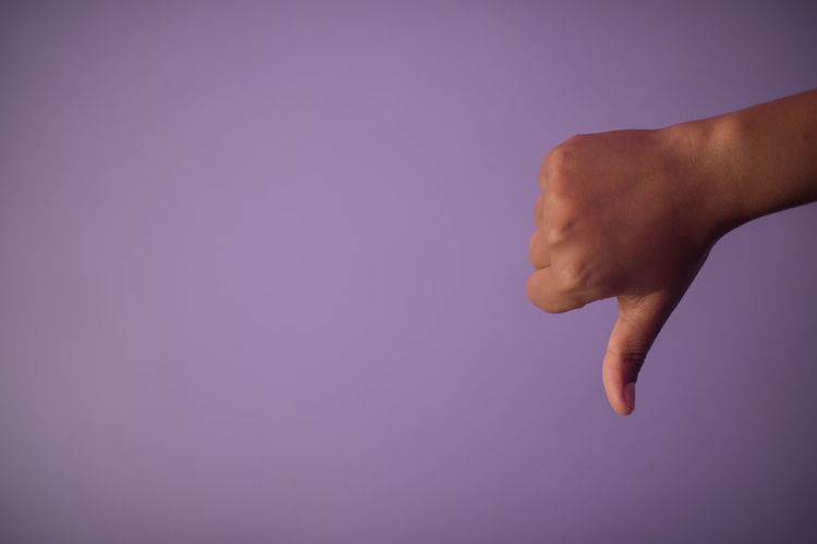 Close-up of hand giving thumbs down