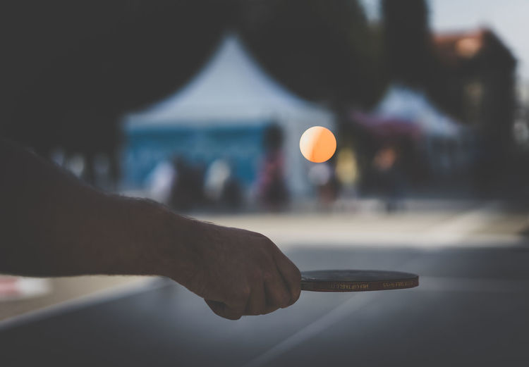 Cropped Image Of Hand Holding Table Tennis Racket During Sunset