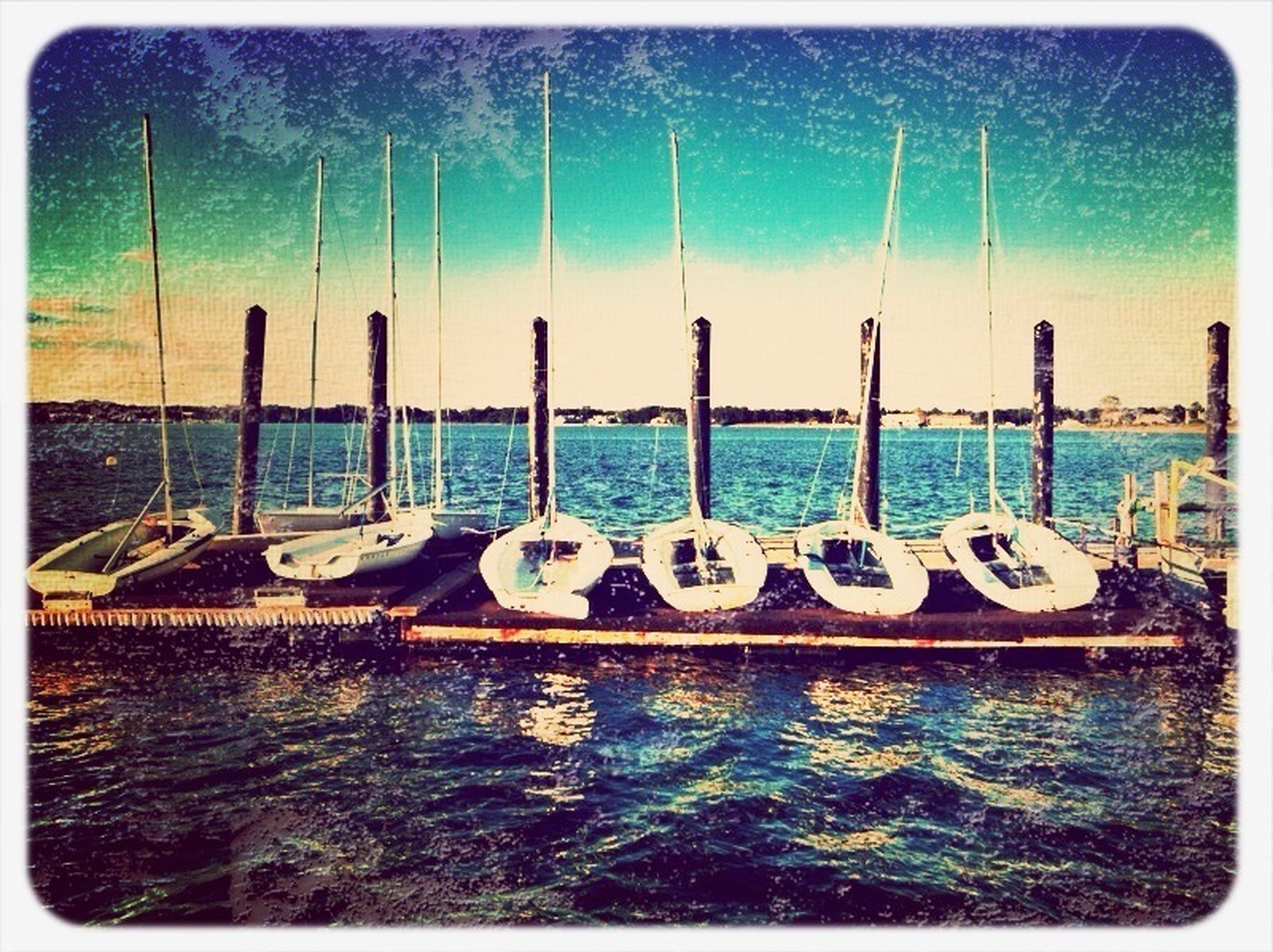 transfer print, water, auto post production filter, sea, blue, nautical vessel, sky, waterfront, panoramic, transportation, day, nature, outdoors, tranquility, moored, no people, in a row, boat, large group of objects, wooden post
