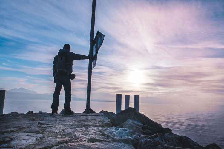 Rear view of man looking at sea while standing on rock against sky during sunset
