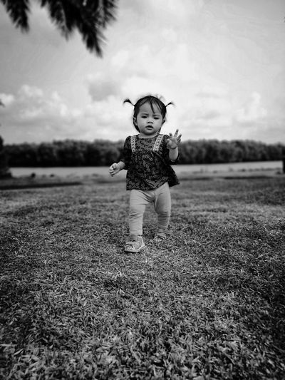 Baby girl walking on field