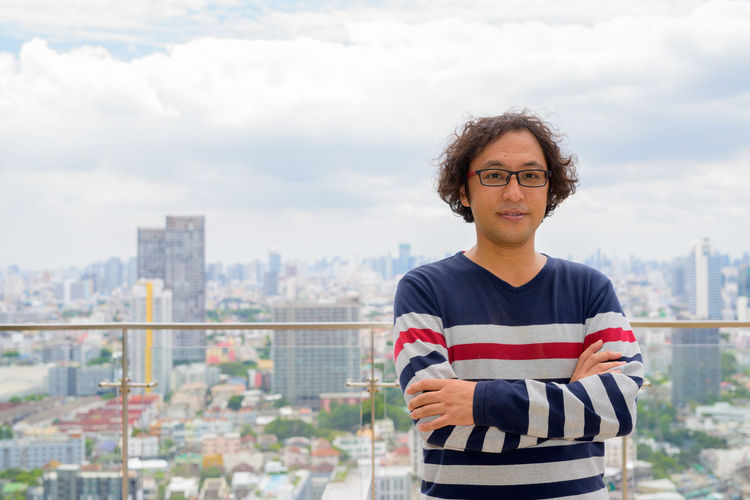 Portrait of smiling man standing against cityscape
