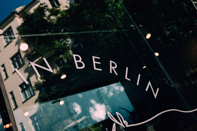 Text Communication Western Script Low Angle View Tree No People Illuminated Plant Architecture Night Window Sign Glass - Material Close-up Outdoors Nature Built Structure Capital Letter Building Exterior In Berlin Berlin Berlin Travel Berlin Postcard