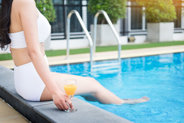 Low Section Of Woman Sitting At Poolside With Orange Juice