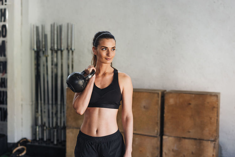 Female Athlete Exercising With Kettlebell In Gym