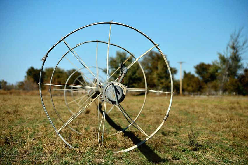 Wheel line irrigation Outdoors Focus On Foreground Blurred Background Trees Eye Level View Sunshine Shadow Wheels Metal Grass