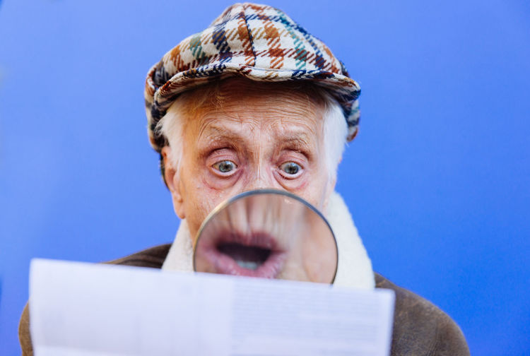 Close-up of senior woman examining paper with magnifying glass against blue background
