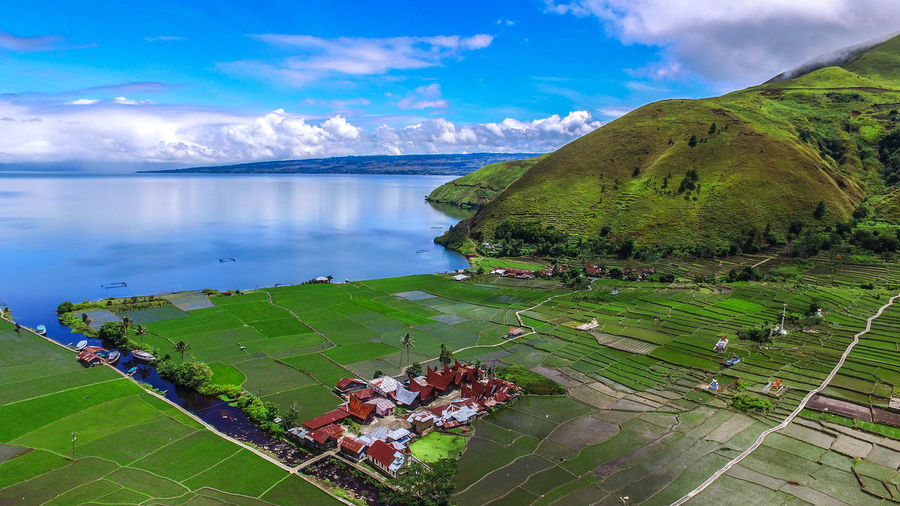 High angle view of agricultural field by mountains against sea