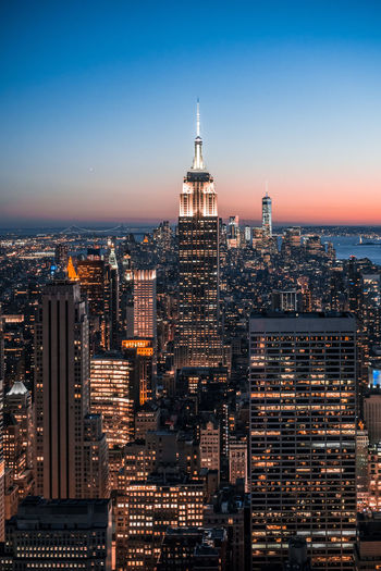 High angle view of illuminated empire state building and cityscape against clear blue sky at night