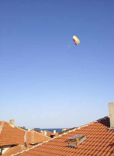 Low angle view of kite flying over building against clear blue sky
