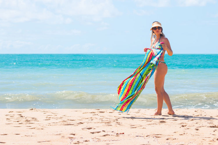 Young Woman In Bikini Holding Colorful Towel At Beach On Sunny Day