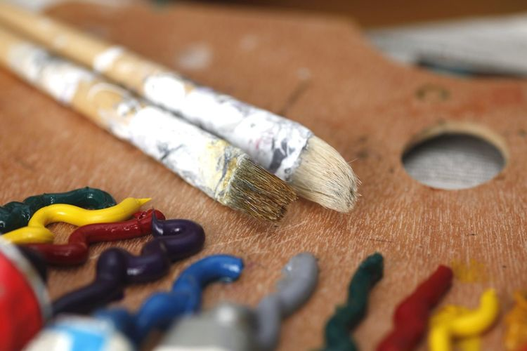 High angle view of colorful paints by brushes on table at workshop
