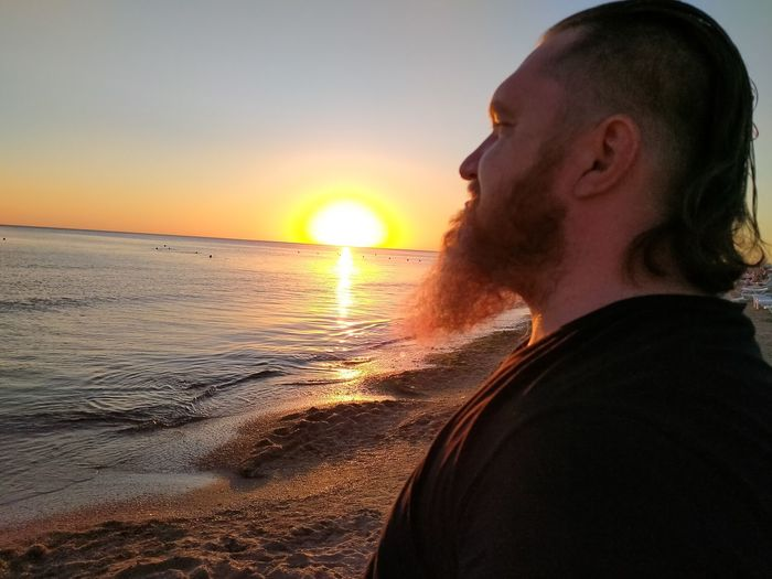 Portrait of young man on beach against sky during sunset