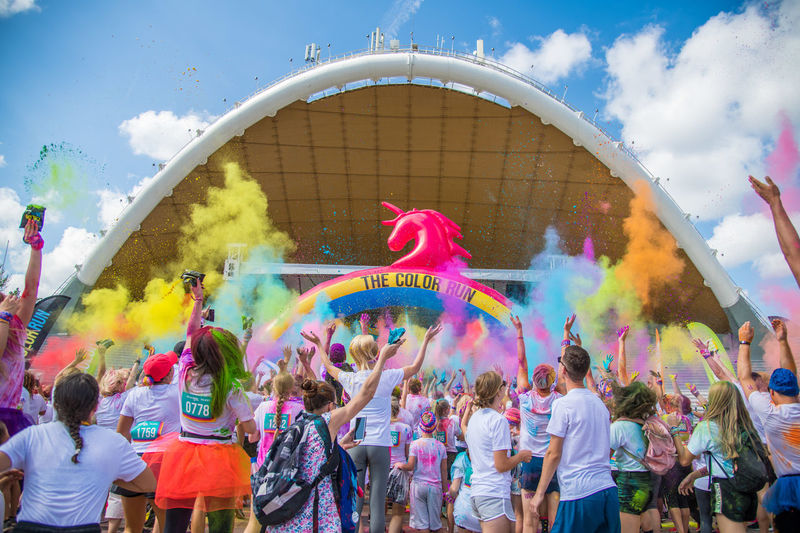 Group of people against rainbow in sky