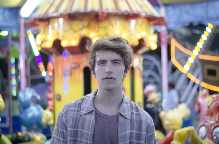 Amusement Park Blogger Boy Carnival Casual Clothing Close-up Day Fair Fashion Focus On Foreground Front View Guy Illuminated Leisure Activity Looking At Camera Neon One Person Outdoors People Portrait Stylish Young Adult Young Men