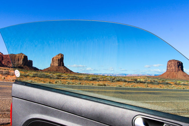 Transportation Car Motor Vehicle Mode Of Transportation Vehicle Interior Land Vehicle Nature Road Car Interior Transparent No People Scenics - Nature Sky Glass - Material Day Blue Travel Rock Desert Windshield Arid Climate Climate Road Trip Car Point Of View Monument Valley Arizona