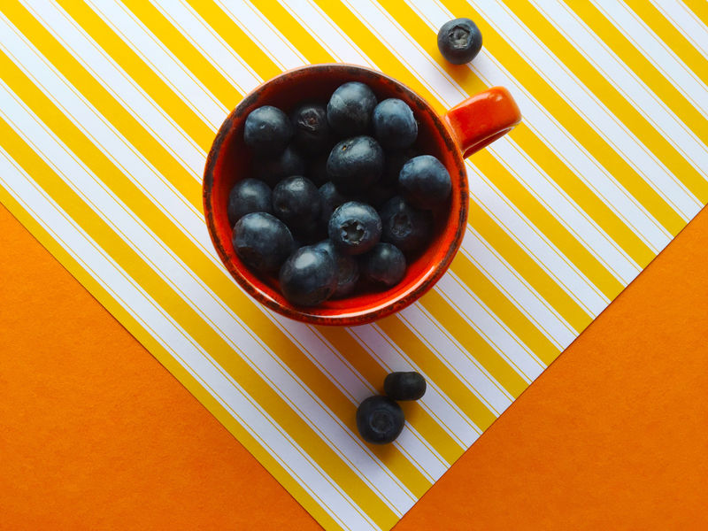 Cup of blueberries on yellow stripes Arrangement Blueberries Colorful Colour Stripes Composition Copy Space Directly Above Food Fresh Fruit Geometric Healthy Eating Indoors  Multi Colored Orange Color Patterns Saturated Still Life Studio Shot Textures Triangles Vibrant Colors Yellow