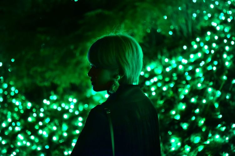 Portrait of man looking at illuminated light