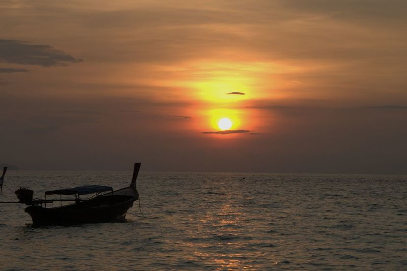 Longtail boat moving on sea against sky during sunset