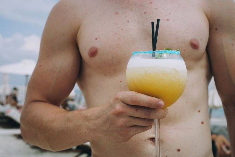 Midsection of shirtless man holding drink