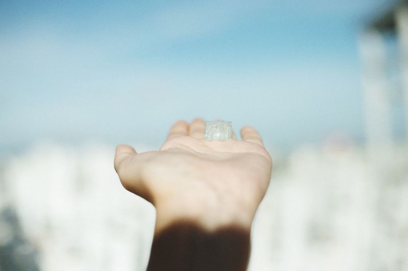 Hand of person holding cube shape against sky