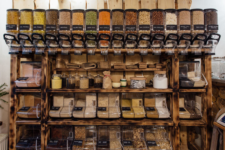 Front view of retail display in grocery plastic free store. Zero waste shopping - shelf with glass containers full of dry food in organic shop. Zero Waste Shop Interior Plastic Free Organic Food Container Dispenser Shelf Rack Waste Free Grocery Refill Dry Food Store Refillable No People Retail  Raw Food Horizontal Nut - Food Coconut Natural Bulk Packaging Healthy Food Variety Alternative Lifestyle Small Business Assortment In A Row Jar Indoors  Full Length Front View Business Side By Side Retail Display