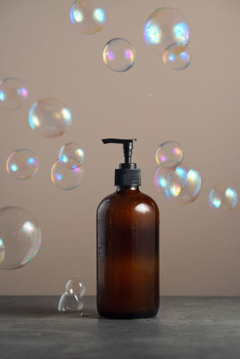 Eco-friendly glass soap dispencer with pump bottle on dark marble with soap bubles around